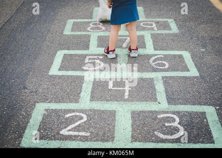 A child stands on a hopscotch, child game, board in a parking lot. - Stock Photo