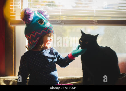 A little girl wearing a winter hat pets a cat while sitting in a sunny window. - Stock Photo