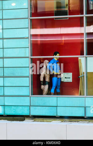 Superman and his friend hiding behind a wall in a department store in Leipzig, Germany. - Stock Photo