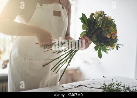 Young female florist trimming a mixed flower bouquet while working at a table in her flower shop - Stock Photo