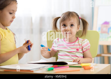 Kids drawing in kindergaten. Children paint in nursery. Preschooler with pen at home. Creative toddlers. - Stock Photo