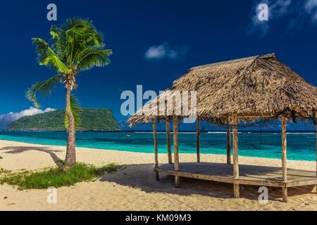 Tropical vibrant natural beach on Samoa Island with palm tree and fale, Upolu - Stock Photo