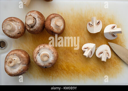 Brown mushrooms on a cutting board with knife in top view - Stock Photo