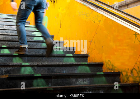 One man legs going up the old city subway stairs in motion blur - Stock Photo