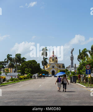 Two middle aged women walk towards the main chapel in Colon Cemetery to attend a funeral during August 2014. - Stock Photo