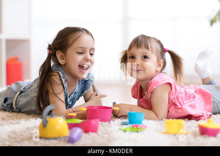 Cute little children playing with kitchenware while lying on floor at home - Stock Photo