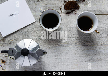 Happy coffee time. Top view of two coffee cups, italian coffee maker-moka and white card with 'Happy' text - Stock Photo