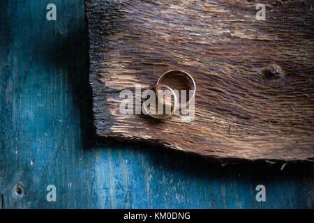 Two wedding rings on rustic wooden background - Stock Photo