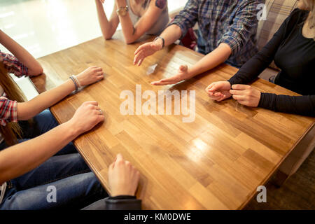 Group of students sitting in a cafe bar looking at each other - Stock Photo