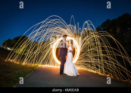 Creative long exposure light painting with bride and groom portraits after a wedding reception. - Stock Photo