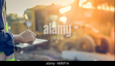 Asian engineer with hardhat using  tablet pc computer inspecting and working at construction site - Stock Photo