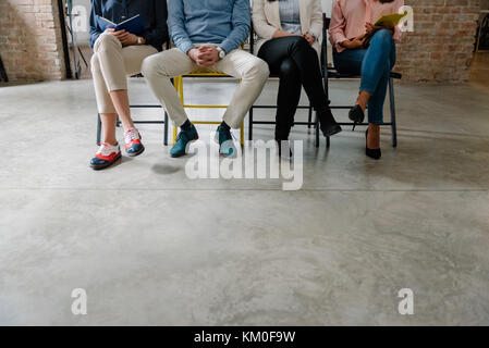 Unemployed people in the waiting room job hunting - Stock Photo