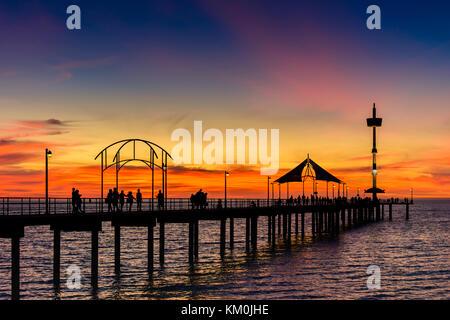 People walking along Brighton Jetty at sunset. South Australia - Stock Photo