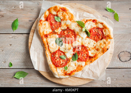 Heart shaped pizza Margherita over wooden background with copy space. Pizza with tomatoes, mozzarella cheese and - Stock Photo