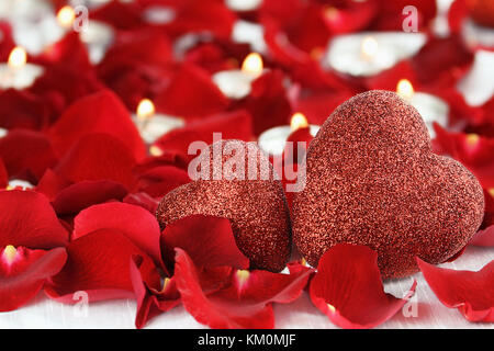 Valentine's Day hearts surrounded by rose petals and lite candles against a white background. Room for copy space - Stock Photo