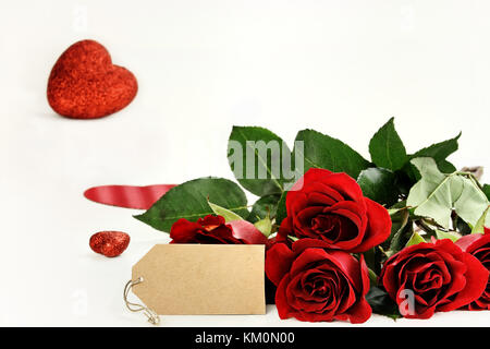 Red roses with an empty label and glitter hearts in the background. Room for copy space with extreme shallow depth - Stock Photo