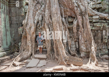 Tourists posing at Ta Prohm in Siem Reap. Built in 12-13th century Ta Prohm temple was later the location for the - Stock Photo