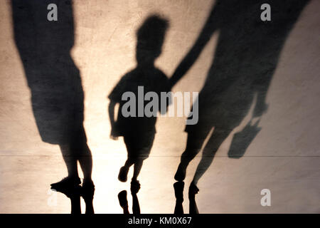 Blurry shadows of mother walking with son hand in hand and a man standing next to them - Stock Photo