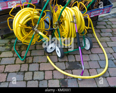 Two market garden hose reels with yellow kink resisting hose on portable reels and having spray nozzles convenient - Stock Photo