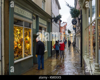 A cold rainy winter's day on Sandgate Whitby with people window shopping for Christmas goods - Stock Photo