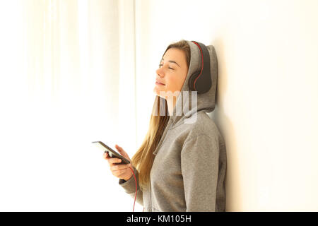 Portrait of a relaxed teen listening to music wearing headphones indoors isolated on white at side - Stock Photo