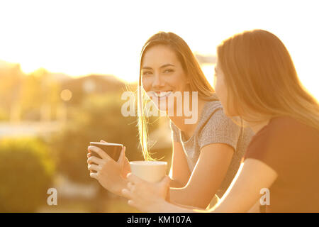 Two happy friends talking outside in a house balcony at sunset - Stock Photo