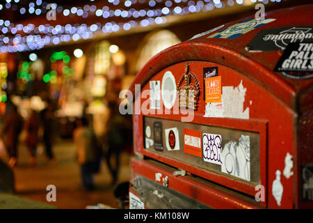 Mail box close up in Camden, London (UK) with blurred Christmas lights on the background. Landscape format. - Stock Photo