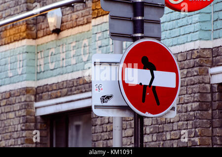 Art sticker on no entry sign in Brick Lane. London, 2016. Landscape format. - Stock Photo