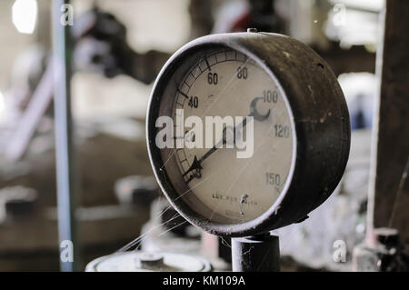 Old pressure gauge on a pump manufactured around 1940. - Stock Photo