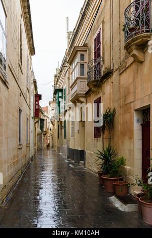 Narrow street in the walled city of Mdina, Malta, in heavy rain. - Stock Photo