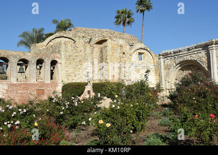 San Juan Capistrano, Ca - December 1, 2017: Mission Bell wall and Serra Statue with the Ruins of the Great Stone - Stock Photo