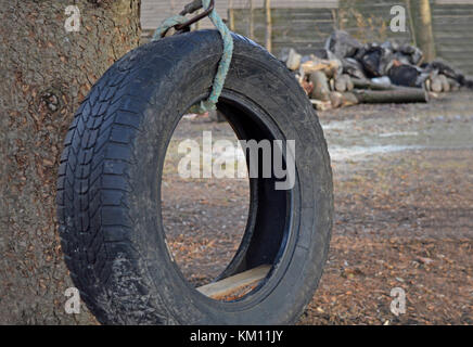 Worn out old tire converted into a to a country swing - Stock Photo