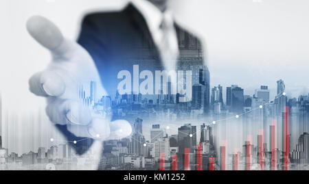 Double exposure Businessman extending hand with buildings in the city and raising graph - Stock Photo