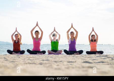 Yoga class at sea beach in evening ,Group of people doing tree poses with clam relax emotion at beach,Meditation - Stock Photo