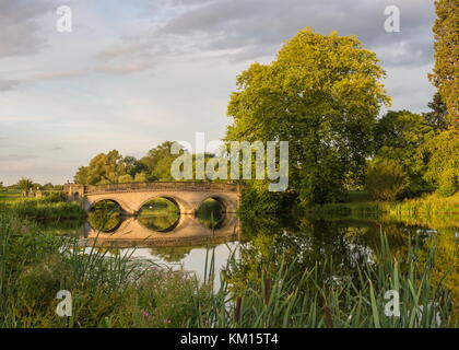 The beautiful sun setting catches a bridge at Compton Verney stately house in Warwickshire - Stock Photo