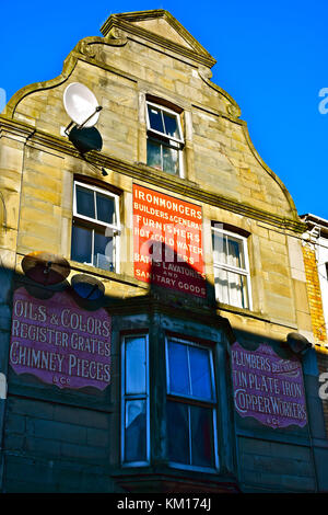 Old Painted Advertising Signs on upper floors of town centre shop in Bridgend,now occupied as Nali's Barber Shop. - Stock Photo