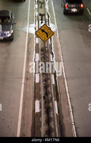 Cars passing by a graffiti that reads in Portuguese 'Attitude', sprayed on yellow board left turn warning traffic - Stock Photo
