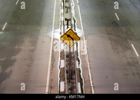 Graffiti that reads in Portuguese 'Attitude', sprayed on yellow board left turn warning traffic sign, Sao Paulo, - Stock Photo
