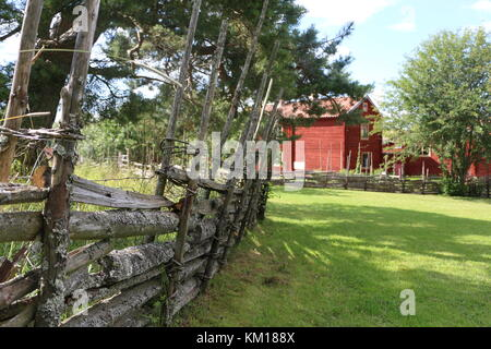 Traditional Swedish wooden fence with red farm house in the background - Stock Photo