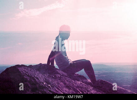Double Exposure of woman on rock looking out at landscape at sunrise - Stock Photo