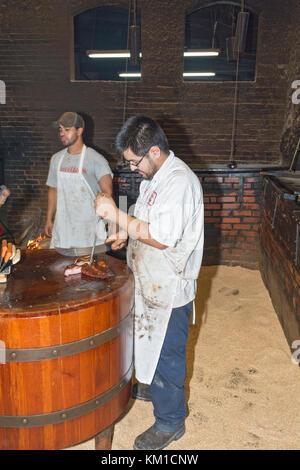 Texas, Caldwell County, Lockhart, Smitty's Market, barbecue restaurant, pit man slicing brisket - Stock Photo