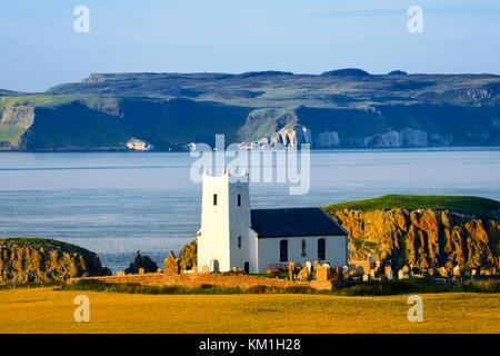 Ballintoy parish church at Ballintoy Harbour near Bushmills on County Antrim coast road. Rathlin Island behind. - Stock Photo