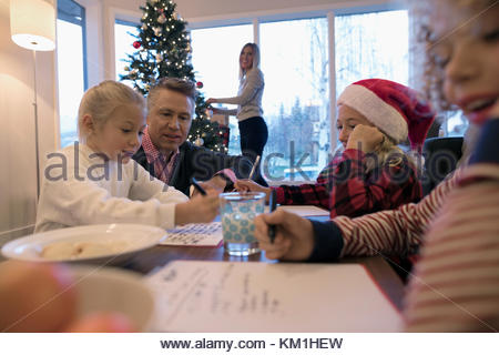 Father watching daughters and son writing Santa letters in Christmas living room - Stock Photo