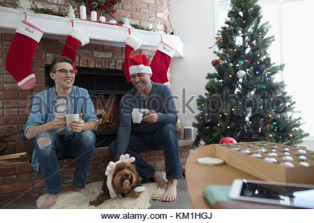 Smiling father and son drinking coffee with dog wearing reindeer antlers in Christmas living room - Stock Photo