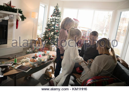 Family opening Christmas gift in living room - Stock Photo