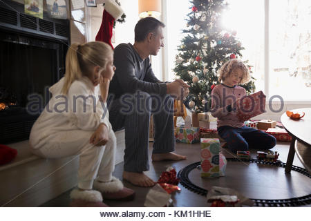 Family opening Christmas gifts in living room - Stock Photo