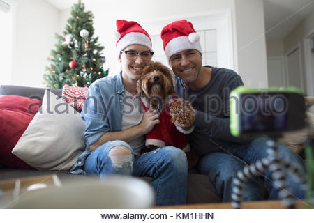 Father, son and dog in Santa hats and costume taking selfie in Christmas living room - Stock Photo