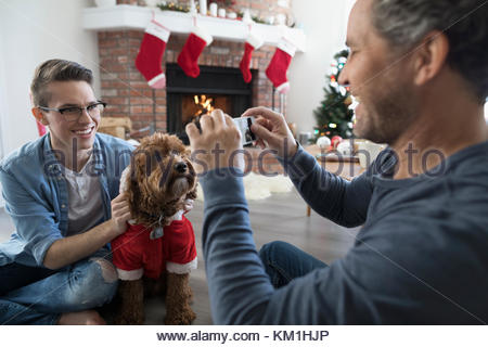 Father with smart phone photographing son and dog in Santa costume in Christmas living room - Stock Photo