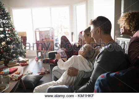 Family taking selfie with digital tablet in Christmas living room - Stock Photo
