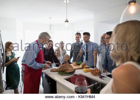Multi-generation family preparing, carving Christmas turkey in kitchen - Stock Photo